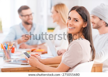 Feeling confident in her team. Beautiful young woman looking over shoulder and smiling while holding mobile phone and sitting together with his colleagues at the wooden table in office - stock photo