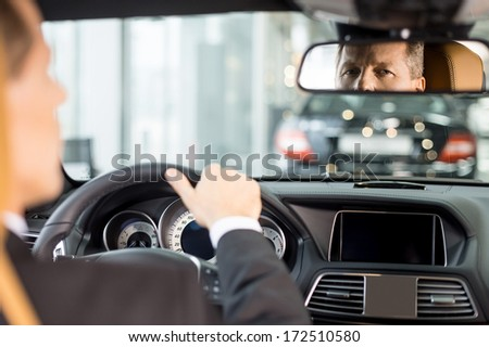 Feeling confident in his new car. Rear view of confident senior man in formalwear sitting on drivers place in car and looking at mirror - stock photo