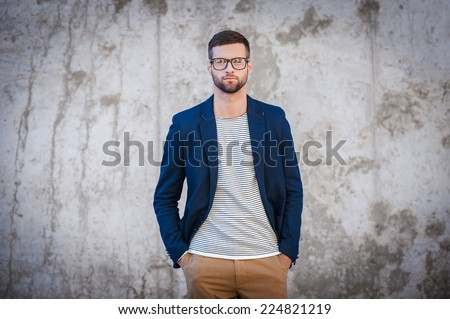 Feeling confident in my skin. Handsome young man in smart jacket holding hands in pockets while standing in front of the concrete wall