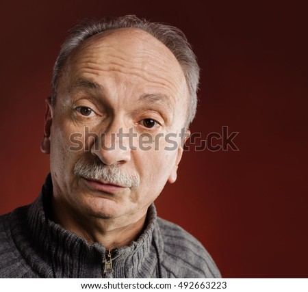 Feeling confused. Portrait of a surprised elderly man on red background