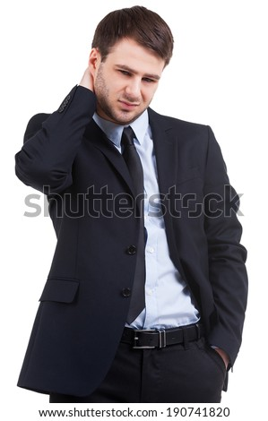 Feeling doubts. Frustrated young man in formalwear touching his neck and looking down while standing isolated on white - stock photo