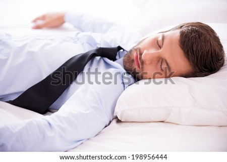 Feeling exhausted after day working. Handsome young man in shirt and tie sleeping in bed  - stock photo