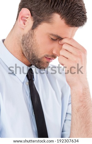 Feeling exhausted. Side view of young man in shirt and tie touching his nose with fingers and keeping eyes closed while standing isolated on white background - stock photo
