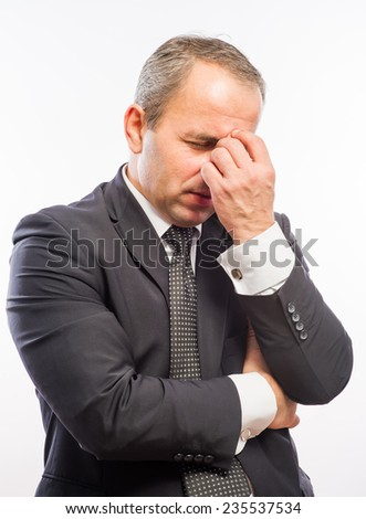 Feeling exhausted. Side view of young man in shirt and tie touching his nose with fingers and keeping eyes closed  - stock photo