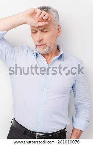 Feeling exhausted. Tired senior man in shirt touching head with hand and keeping eyes closed while standing against white background - stock photo