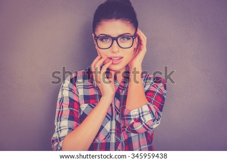 Feeling flirty. Beautiful young woman in eyeglasses holding finger in mouth and looking at camera while standing against grey background - stock photo