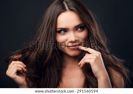 Feeling flirty. Cheerful young shirtless woman holding one hand in hair and touching her lips and while standing against black background   - stock photo