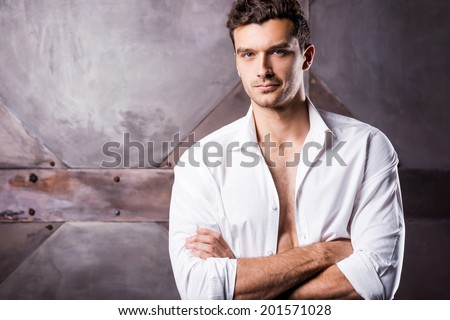 Feeling flirty. Handsome young man in unbuttoned shirt keeping arms crossed and looking at camera  - stock photo