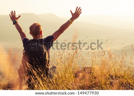 Feeling freedom man greeting golden rising of the sun - stock photo