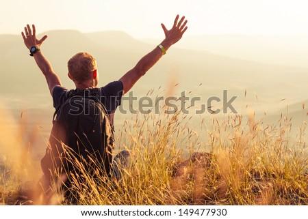 Feeling freedom man greeting golden rising of the sun - stock photo
