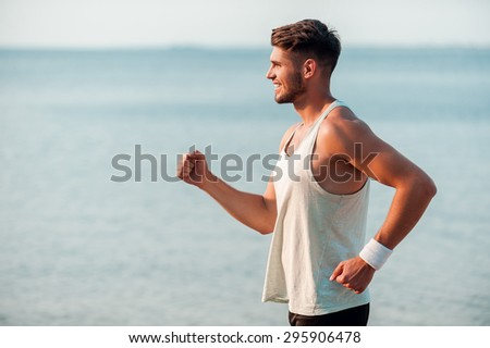 Feeling good and keeping fit. Side view of smiling young muscular man running along the riverbank - stock photo