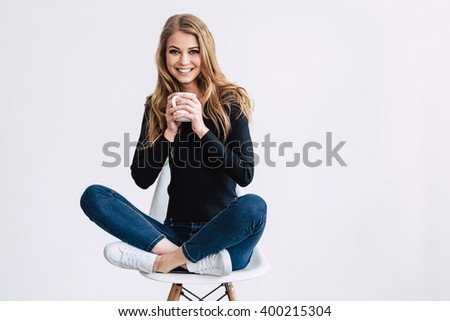 Feeling great. Beautiful young woman holding coffee cup and looking at camera with smile while sitting on chair in lotus position against white background - stock photo