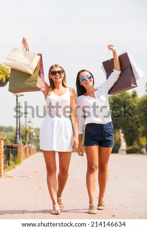 Feeling happy after day shopping. Full length of two beautiful young women showing their shopping bags and smiling while walking by the street together - stock photo