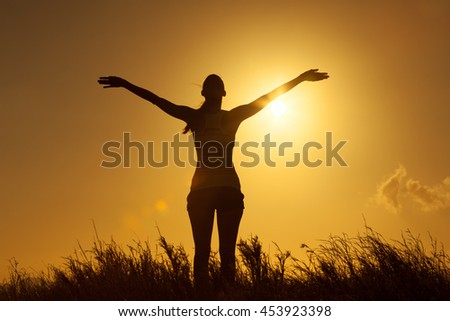 Feeling happy and free ! Woman in a open field with her hands out stretched into the beautiful sky.  - stock photo