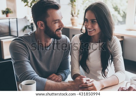 Feeling happy now. Happy young loving couple holding hands and looking at each other while sitting at the desk with some man sitting in front of them  - stock photo