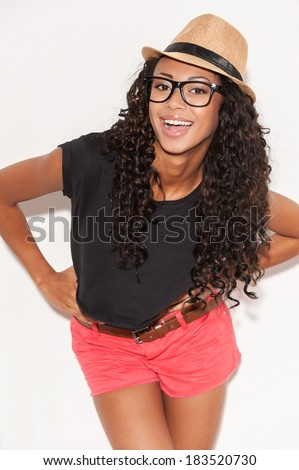 Feeling happy with her style. Beautiful young African woman in glasses and funky wear holding hands on hip and smiling at camera while posing against white background - stock photo