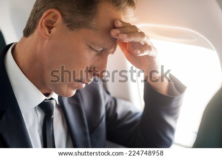 Feeling headache. Frustrated mature businessman touching his forehead with hand and keeping eyes closed while sitting at his seat in airplane  - stock photo