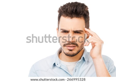 Feeling headache. Frustrated young man in shirt touching head and looking at camera while standing against white background - stock photo