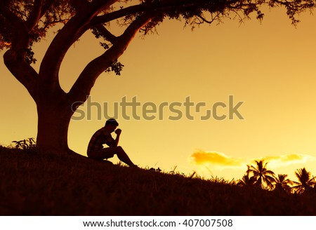 Feeling lonely. Young man siting under a tree with his hands on clasped together.