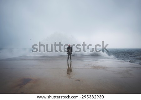 Feeling of freedom, back view of adult man standing on pier facing to the sea with big waves beats against the shore on a cloudy autumn day, alone depress person,the power of nature, storm on seashore - stock photo