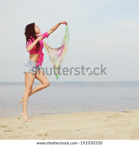 Feeling of freedom, young brunette woman by the sea.