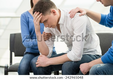 Feeling pain and depression. Depressed young man is sitting at the chair while two other people are comforting his. - stock photo