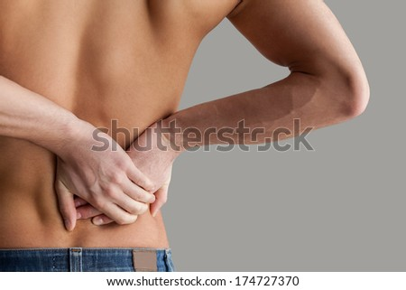 Feeling pain in back. Cropped image of young muscular man touching his back while standing isolated on grey background - stock photo