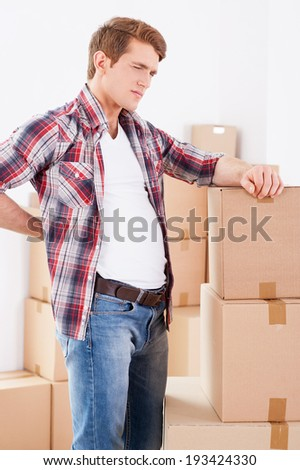 Feeling pain in back. Young man holding hand on his back and expressing negativity while leaning at the cardboard box - stock photo