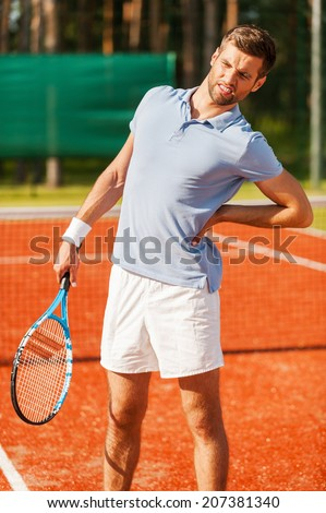 Feeling pain in his back. Close-up of tennis player touching his back and grimacing while standing on the tennis court - stock photo