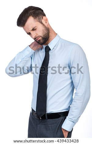 Feeling pain in neck. Frustrated young man in shirt and tie massaging his neck and keeping eyes closed while standing against white background  - stock photo