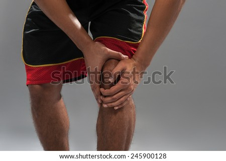 Feeling pain in the knee. Closeup of young muscular African man touching his knee after basketball play while standing against grey background - stock photo