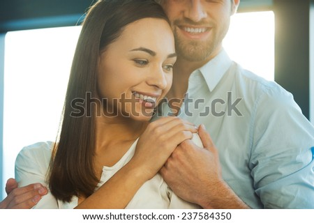 Feeling protected near him. Beautiful young loving couple bonding to each other and holding hands - stock photo