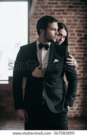 Feeling protected near him. Beautiful young woman standing behind her boyfriend and looking over his shoulder while both standing indoors  - stock photo