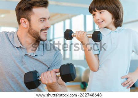 Feeling proud of his son. Happy father and son exercising with dumbbells and smiling while standing in health club together - stock photo