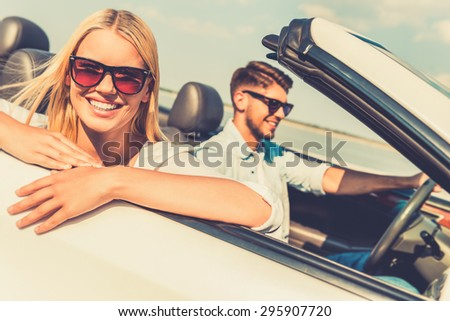 Feeling relaxed and free. Happy young woman leaning at the vehicle door and looking at camera while her boyfriend sitting near and driving convertible  - stock photo