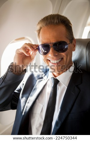 Feeling safe and comfortable. Cheerful mature businessman sitting at his seat in airplane and adjusting his sunglasses - stock photo