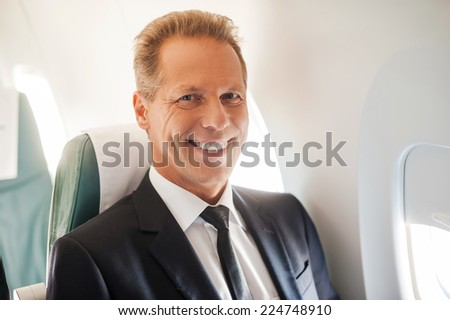 Feeling safe and comfortable. Confident mature businessman sitting at his seat in airplane and smiling - stock photo