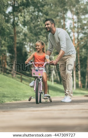 Feeling safe near father. Full length of cheerful father teaching his daughter to ride a bicycle in park