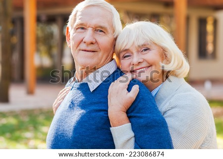 Feeling safe near him. Happy senior couple bonding to each other and smiling while standing outdoors and in front of their house  - stock photo