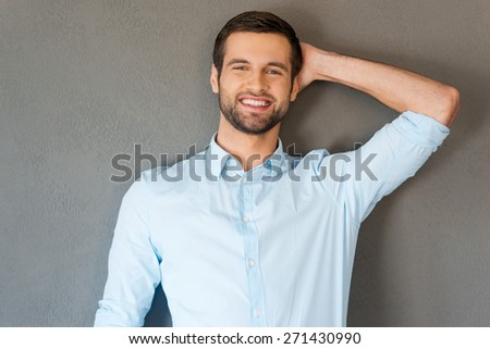 Feeling satisfied and relaxed. Handsome young man in shirt touching his head and smiling at camera while standing against grey background  - stock photo