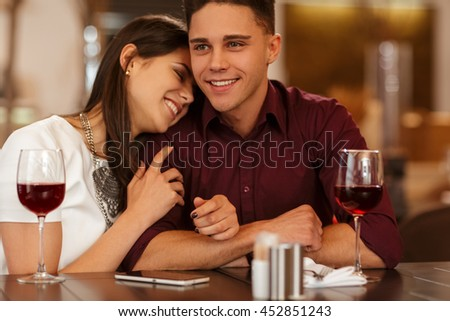 Feeling secure with him. Young happy beautiful woman laying her head on the shoulder of her smiling handsome man laughing with her eyes closed on a date at the restaurant