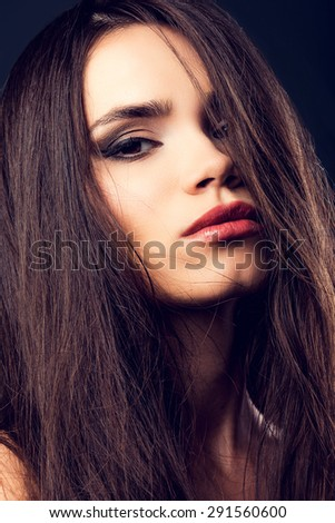 Feeling seductive. Attractive young woman looking at camera and covering half of face by hair while standing against black background   - stock photo