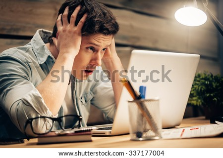 Feeling sick and tired. Frustrated young man holding head in hands and looking at laptop while working late at his working place - stock photo