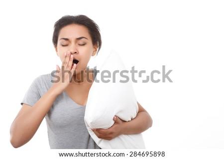 Feeling sleepy. Beautiful young mulatto girl standing on white isolated background and yawning - stock photo