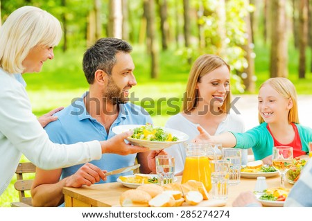 Feeling so hungry! Happy family enjoying meal together while senior woman passing a plate with salad to a little girl - stock photo