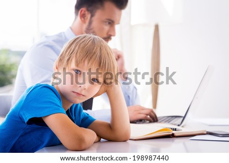 Feeling so lonely. Sad little boy holding hand in hair and looking at camera while his busy father working in the background  - stock photo