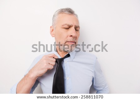 Feeling so tired. Tired senior man in shirt taking off his necktie while standing against white background - stock photo