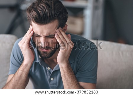 Feeling stressed. Frustrated handsome young man touching his head and keeping eyes closed while sitting on the couch at home - stock photo