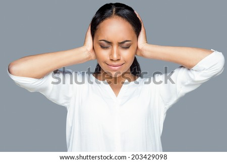 Feeling tired and stressed. Frustrated young African woman covering ears with hands and keeping eyes closed while standing against grey background - stock photo