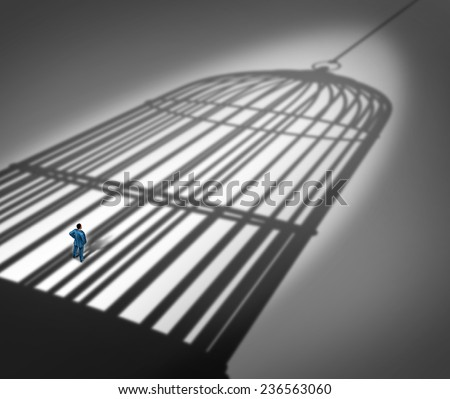 Feeling trapped in a prison concept as a person standing inside the cast shadow of a giant bird cage as a metaphor for business career frustration or human repression metaphor. - stock photo